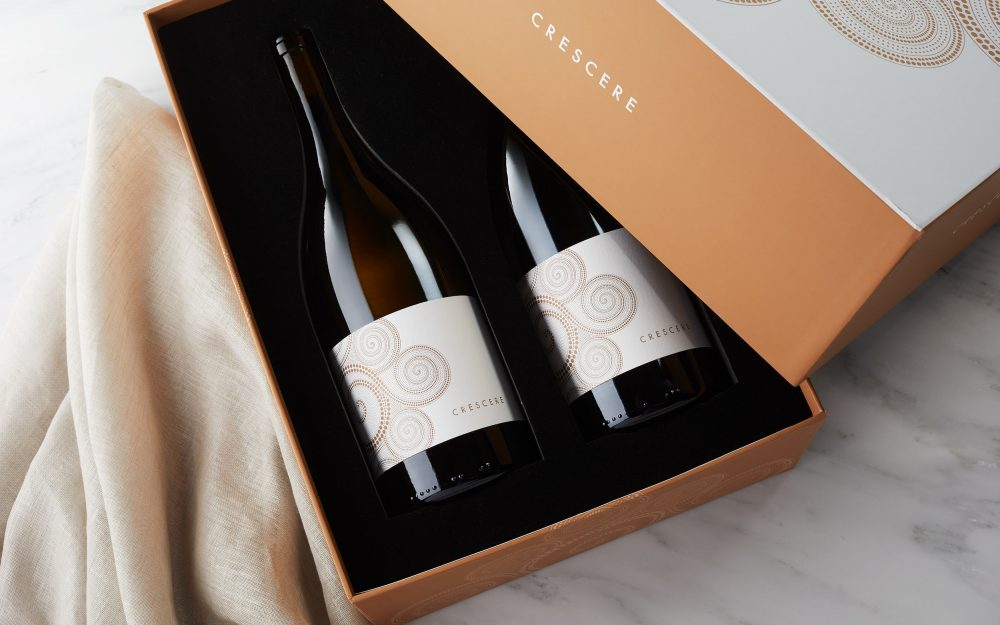 Two bottles of Crescere wines in cream and tan Crescere box